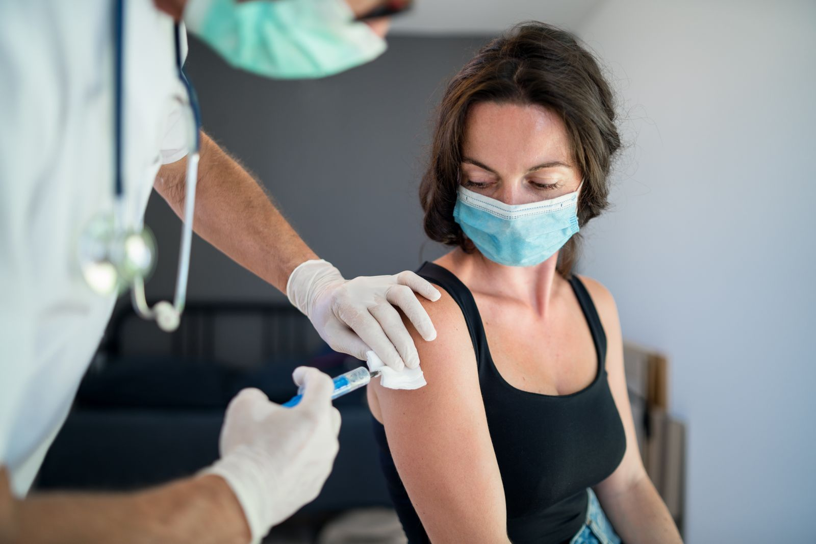 Woman with face mask getting vaccinated, coronavirus concept.