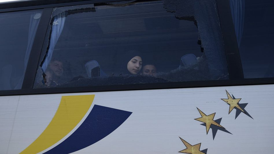 Flüchtlinge hinter einem zerbrochenen Busfenster in Griechenland
