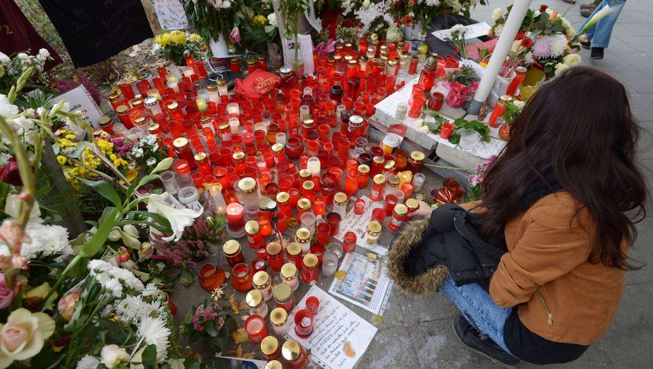 Gedenken an Prügelopfer vom Alexanderplatz: Eine junge Frau zündet eine Kerze an