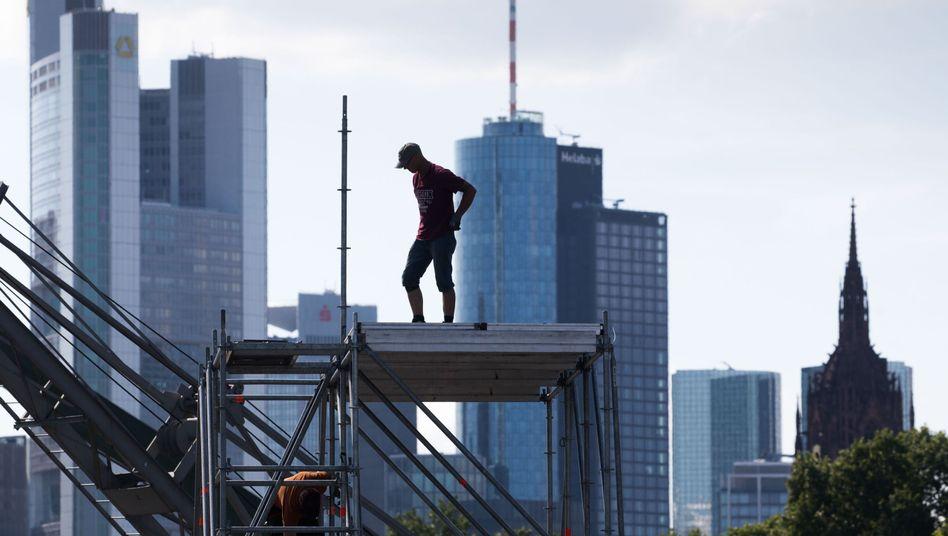Arbeiter vor Frankfurter Bankenskyline