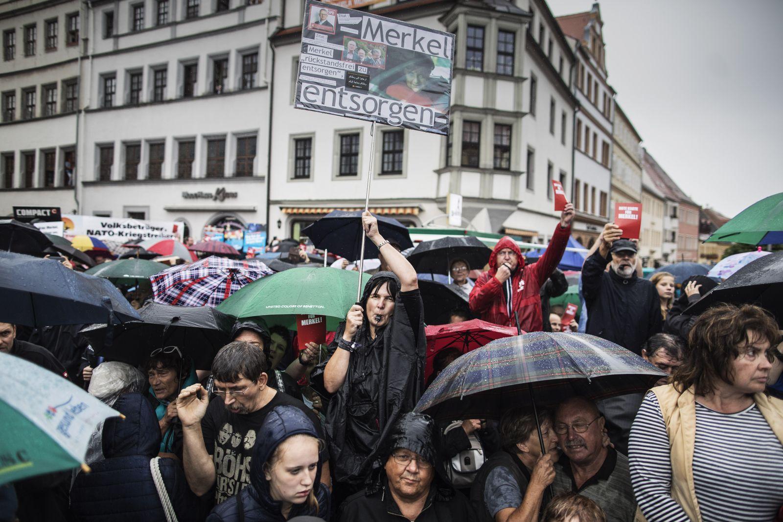 EINMALIGE VERWENDUNG Angela Merkel faces AfD protestors in Torgau