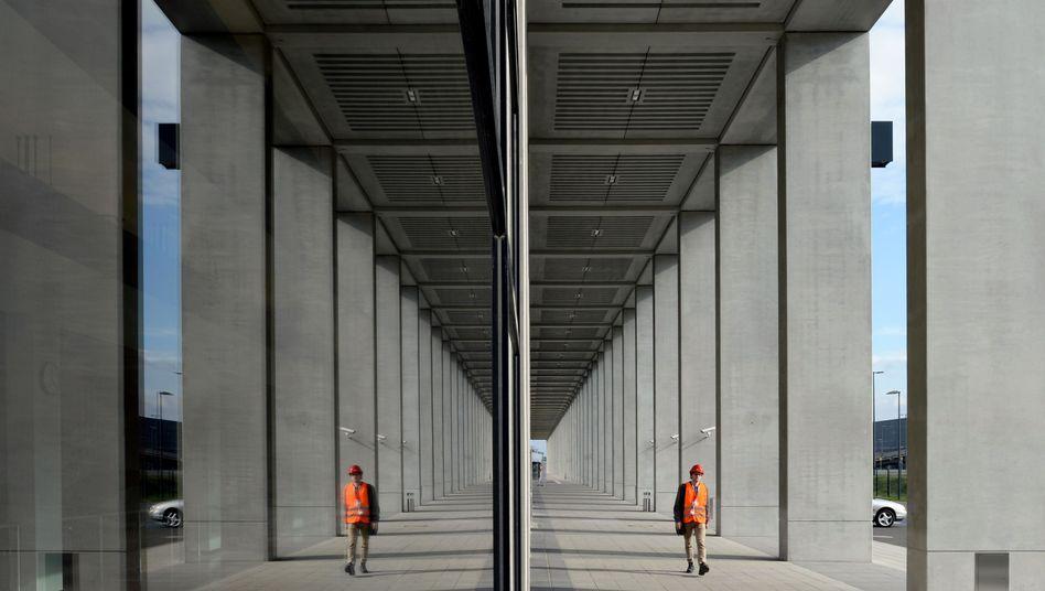 Arbeiter vor Abflughalle des BER: Kosten steuern auf sechs Milliarden Euro zu