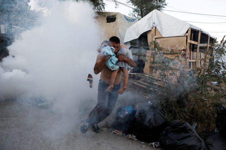 Feuer im Flüchtlingslager: Ein Mann flieht mit einem Kind vor dem Tränengas der Polizei. Nach einem Brand waren auf Lesbos Proteste ausgebrochen