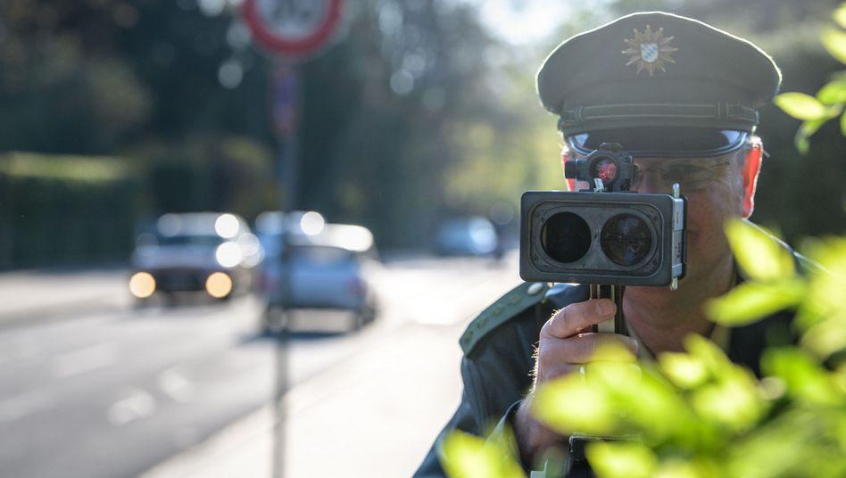 Ein Polizist misst mit einer Laserpistole die Geschwindigkeit vorbeifahrender Fahrzeuge