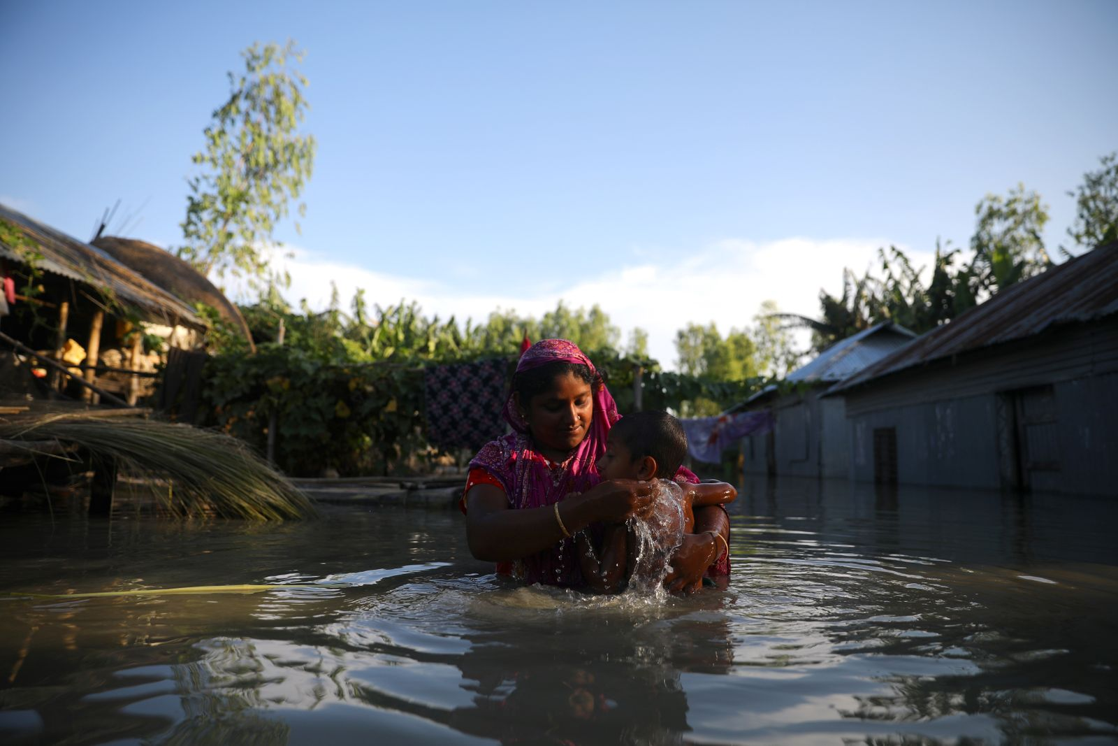 A flood-affected woman bathes her child in flood water in Bogura