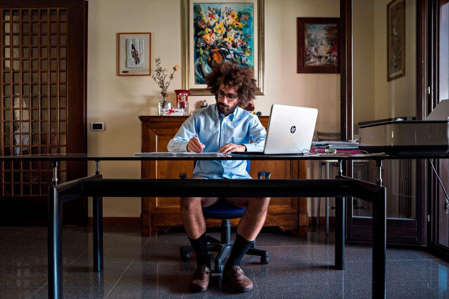 Hinter den Kulissen sieht die neue Normalität auch für viele junge Italiener unvollständig aus. Der 30-jährige Pietro zeigte sich dem Fotografen bewusst in Boxershorts am Schreibtisch