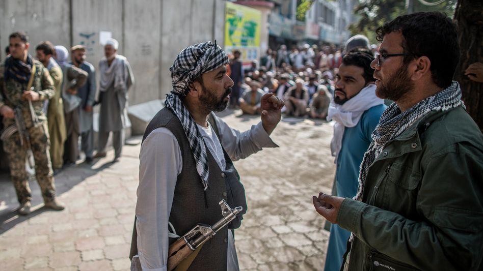 Ein Mitglied der Taliban unterhält sich mit einem Afghanen in Kabul (Symbolbild)