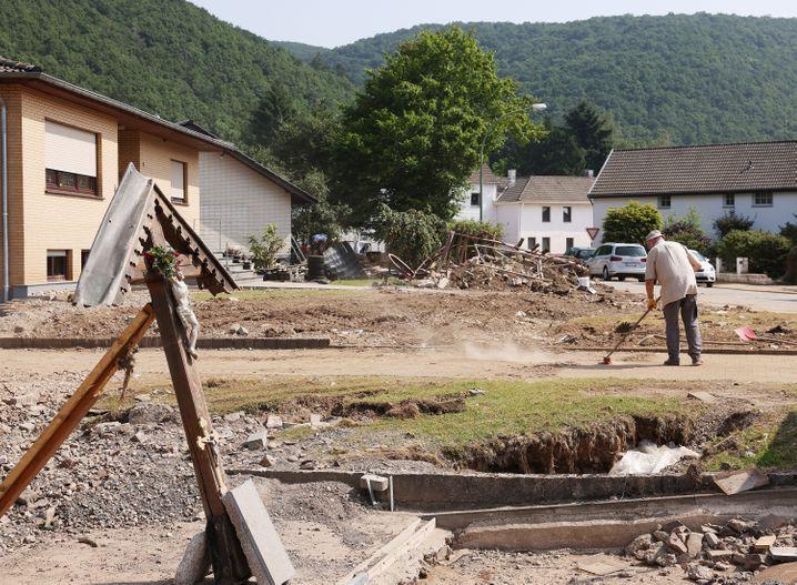 Die Eifel nach dem Hochwasser: Ein Mann räumt vor seinem Haus auf
