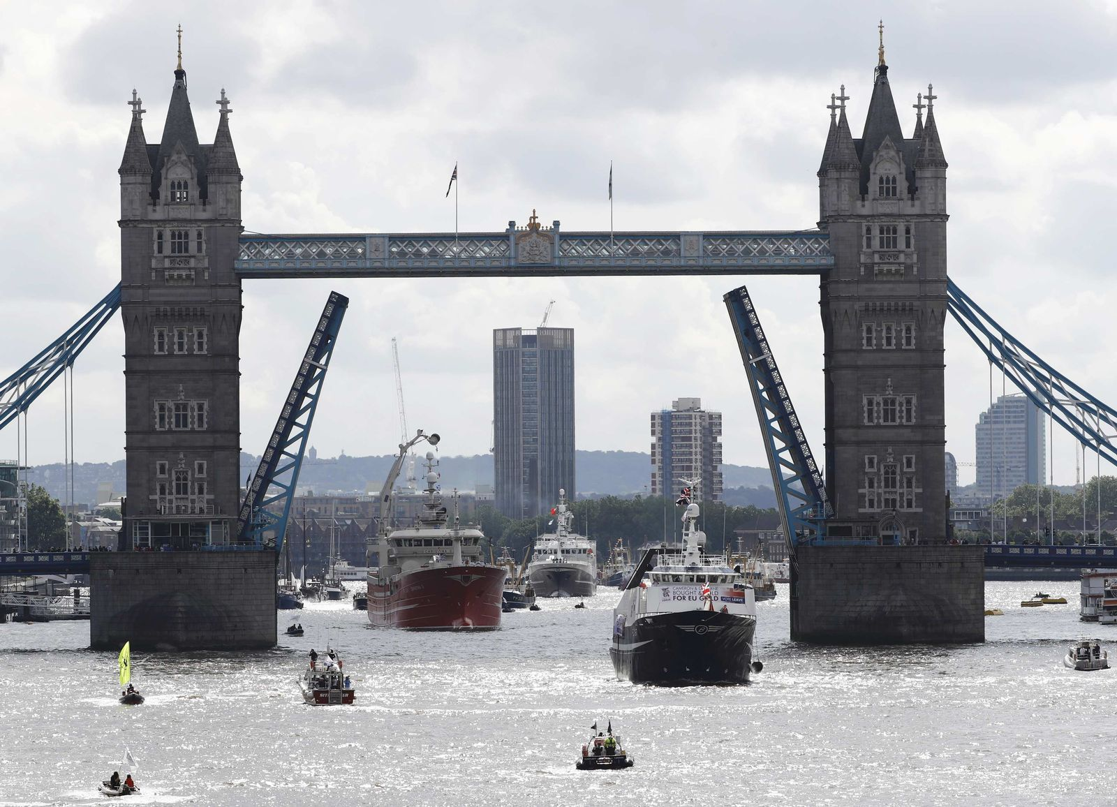 A pro-Remain inflatable dinghy sails in front of a flotilla of fishing vessels campaigning to leave the European Union as it sails under Tower Bridge on its way up the river Thames in London