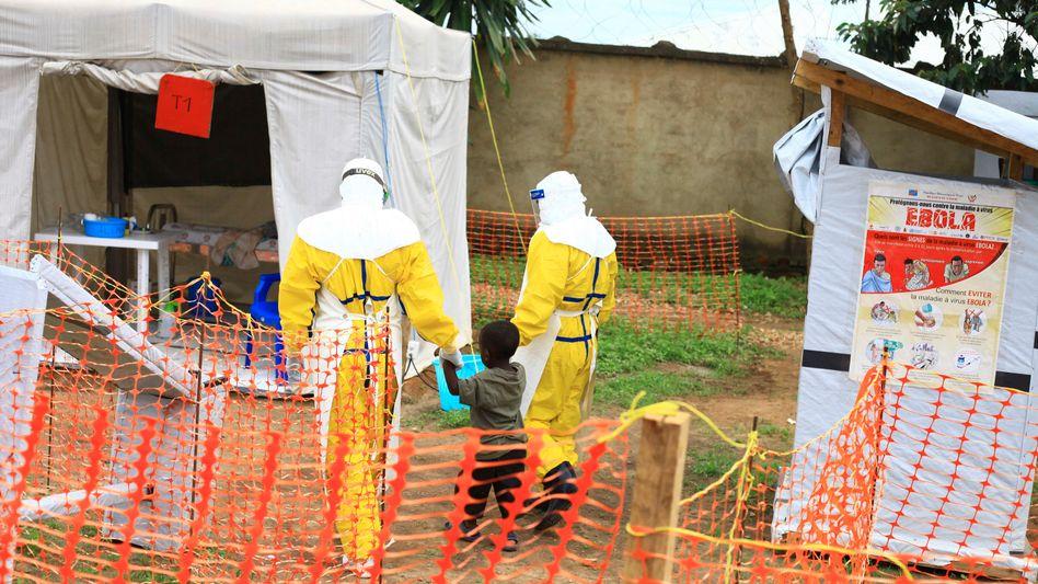 Mitarbeiter des Gesundheitsamtes mit einem Jungen, der sich mutmaßlich mit Ebola infiziert hat