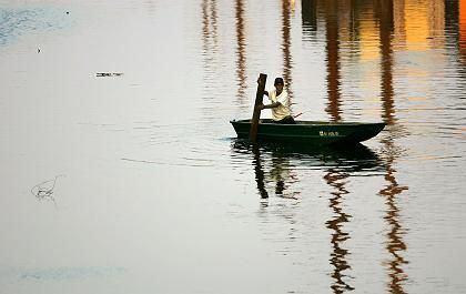 A man rowing through the streets of New Orleans a full week after Hurricane Katrina devastated the city.