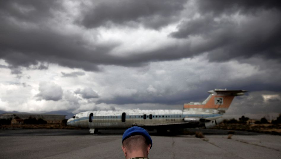 A UN soldier stands in front of a destroyed Cyprus airways plane at the war-torn buffer zone at the abandoned Nicosia airport in the divided capital.
