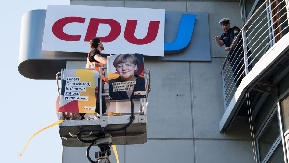 Ein Demonstrant bringt ein CDU-Logo an der CSU-Zentrale an