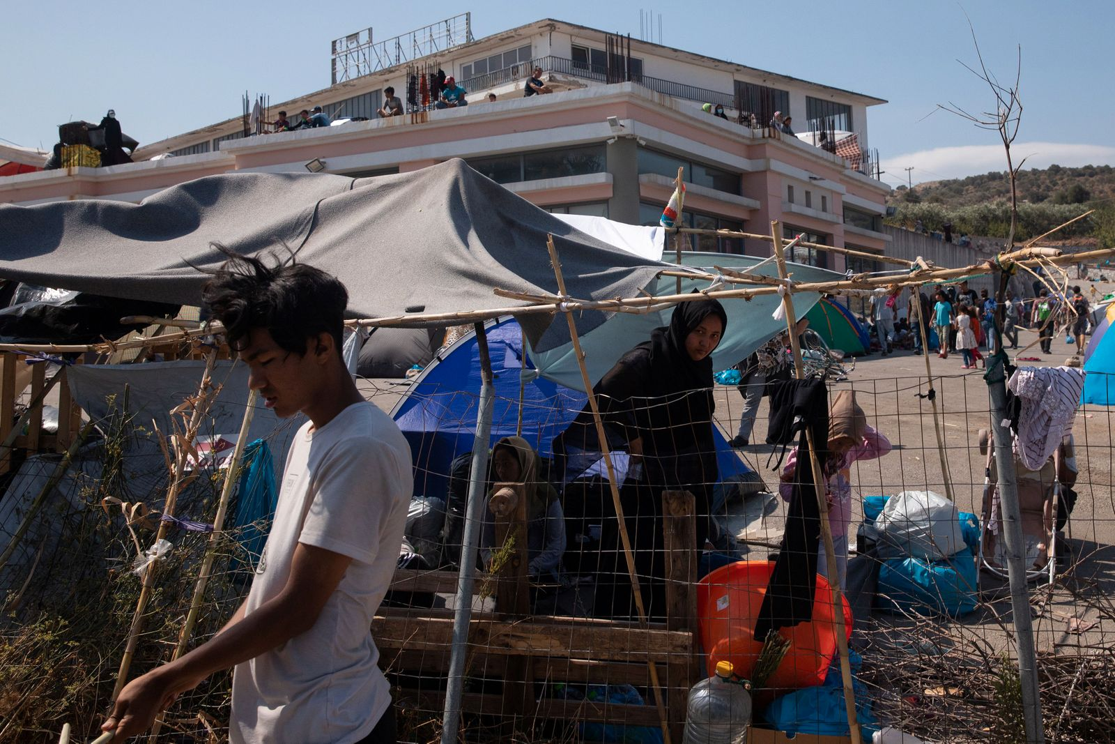 Refugees and migrants from the destroyed Moria camp are seen in the premises of an abandoned building, near a new temporary camp, on the island of Lesbos