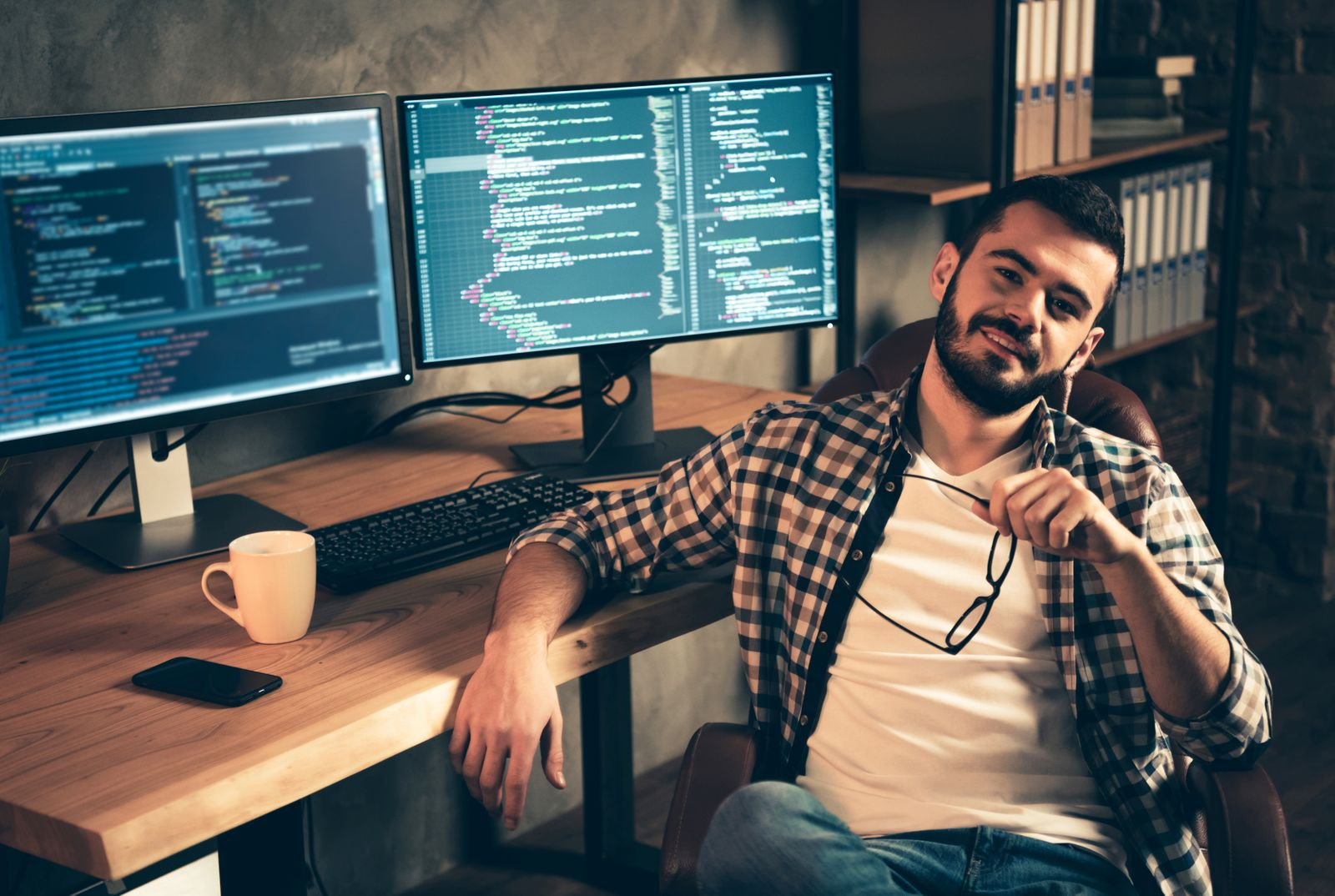 Portrait of his he nice attractive confident content bearded guy wearing checked shirt expert specialist nerd shark boss genius at wooden industrial interior work place station