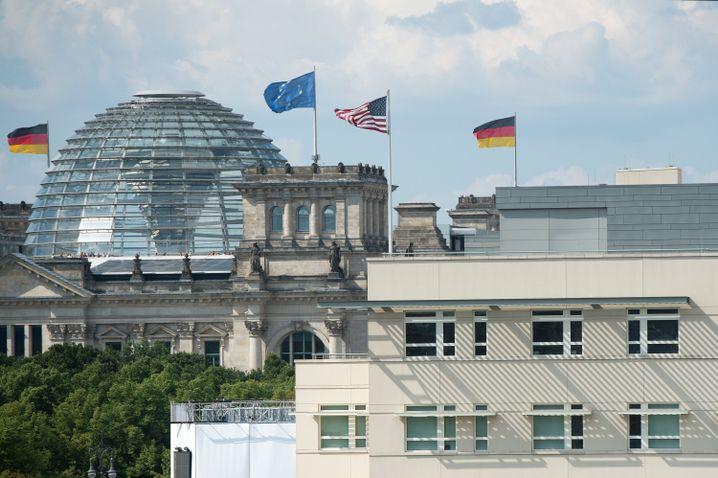 US-Flagge über der US-Botschaft in Berlin. Im Hintergrund ist der Reichstag zu sehen.