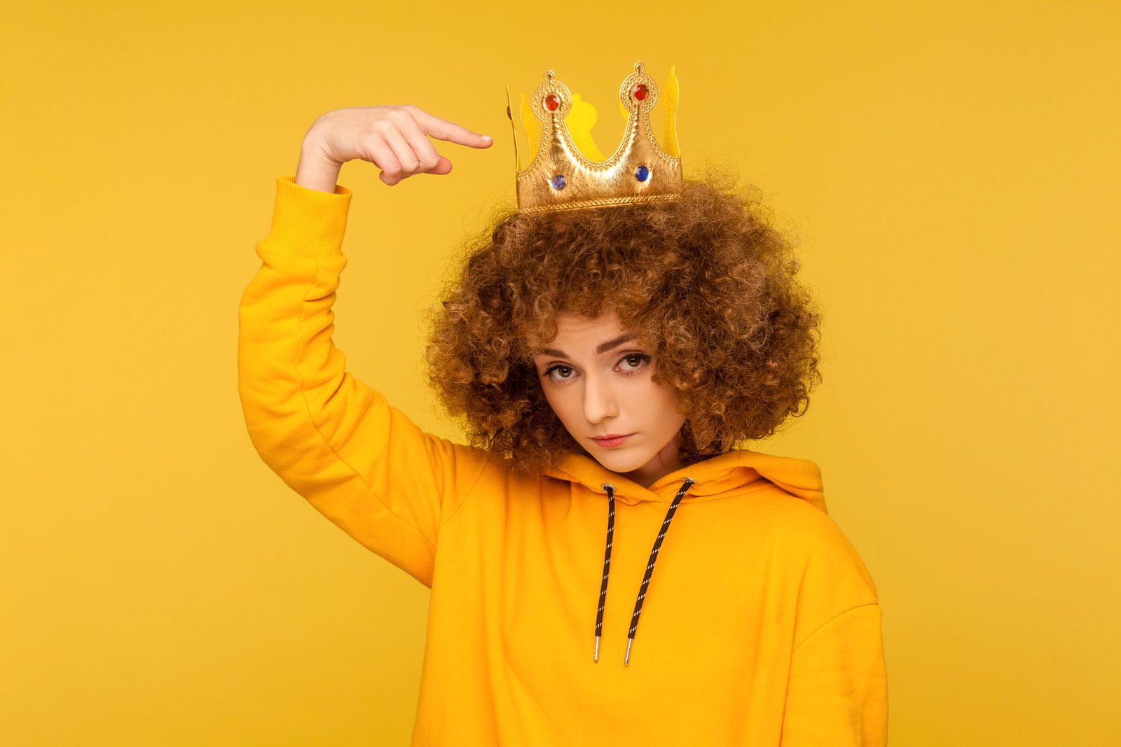 Look, I am best! Selfish haughty curly-haired woman pointing at crown on head and looking with arrogance