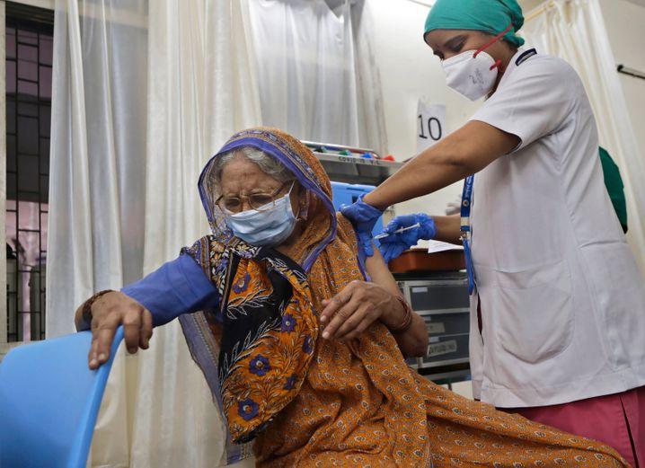 In Teilen von Indien, das von der Pandemie besonders betroffen ist, stabilisiert sich die Lage nach offiziellen Angaben. Für eine Entwarnung sei es jedoch noch zu früh, sagt ein Mitglied des Coronakrisenstabs der indischen Bundesregierung. »Während es sich in vielen Teilen des Landes stabilisiert hat und die Belastung sich insgesamt verringert hat, müssen wir noch einen langen Weg mit dieser Welle gehen«, sagt der Krisenmanager Dr. V. K. Paul. Auf dem Bild ist eine Frau aus Mumbai zu sehen, die gerade geimpft wird.