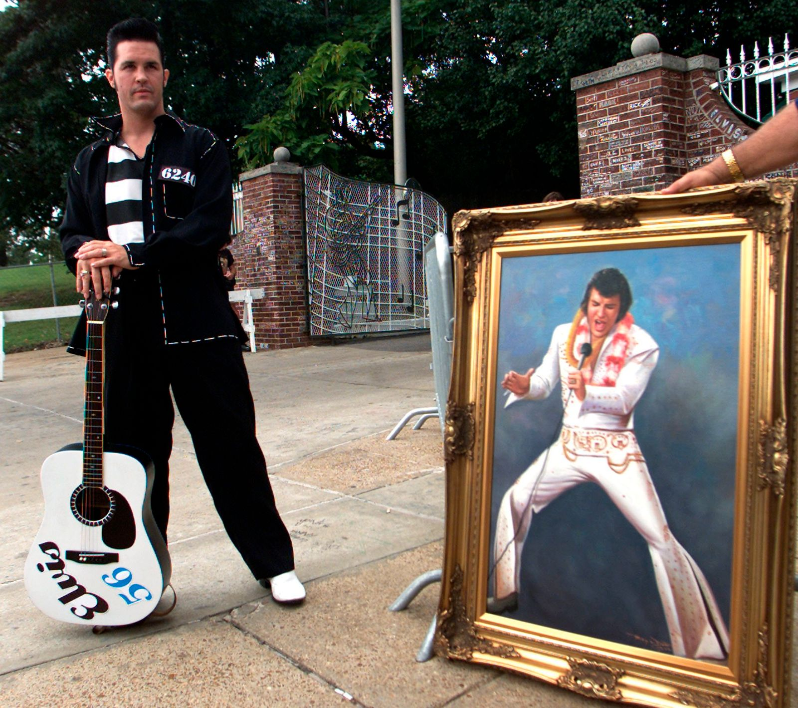 An Elvis Presley fan Randall Houser of Cincinnatti, Ohio stands near a painting of Presley, in front of the gate of the Presley's Graceland home in Memphis, Tennessee