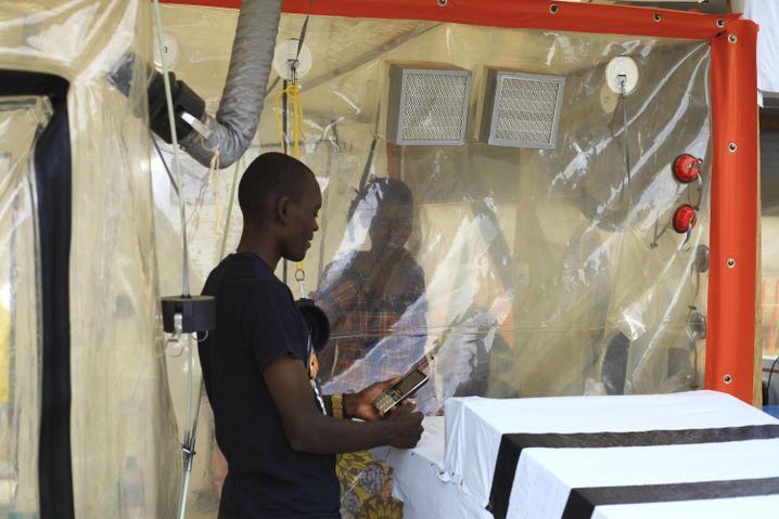 Kasereka Mulanda spricht mit seiner Frau, die sich aufgrund einer Infektion mit dem Ebolavirus in einer Isolationszelle befindet.