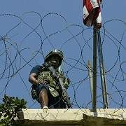 A US soldier stands guard on the roof of the US Embassy in Damascus on Sept. 12 following a brazen daylight attack on the building.