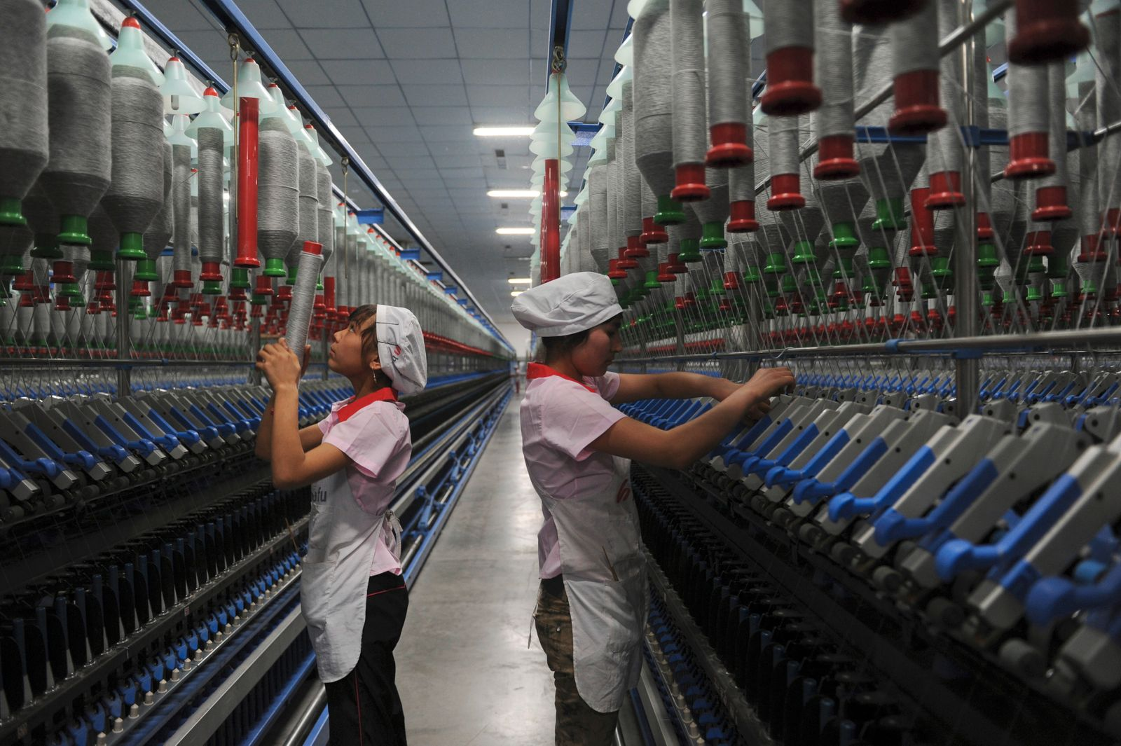 Uighur ethnic minority employees work at the production line of a textile mill in Aksu