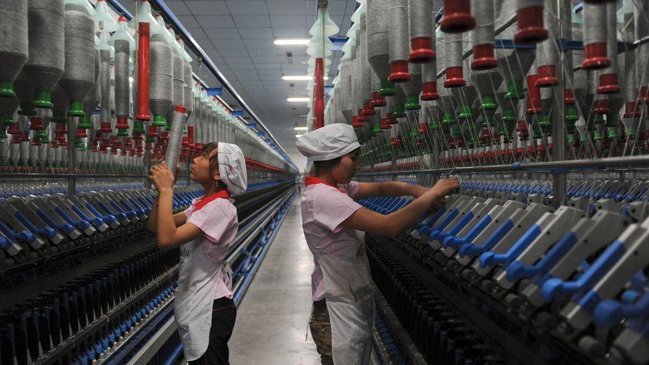 Uiguren in einer Textilfabrik in Xinjiang (2012): Verschickt Peking nun Zwangsarbeiter über die Provinz hinaus?