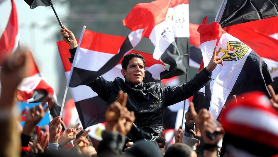 Tahrir square in Cairo: Egyptians hold their national flags as they take part in a rally celebrating the first anniversary of the 25th January uprising.