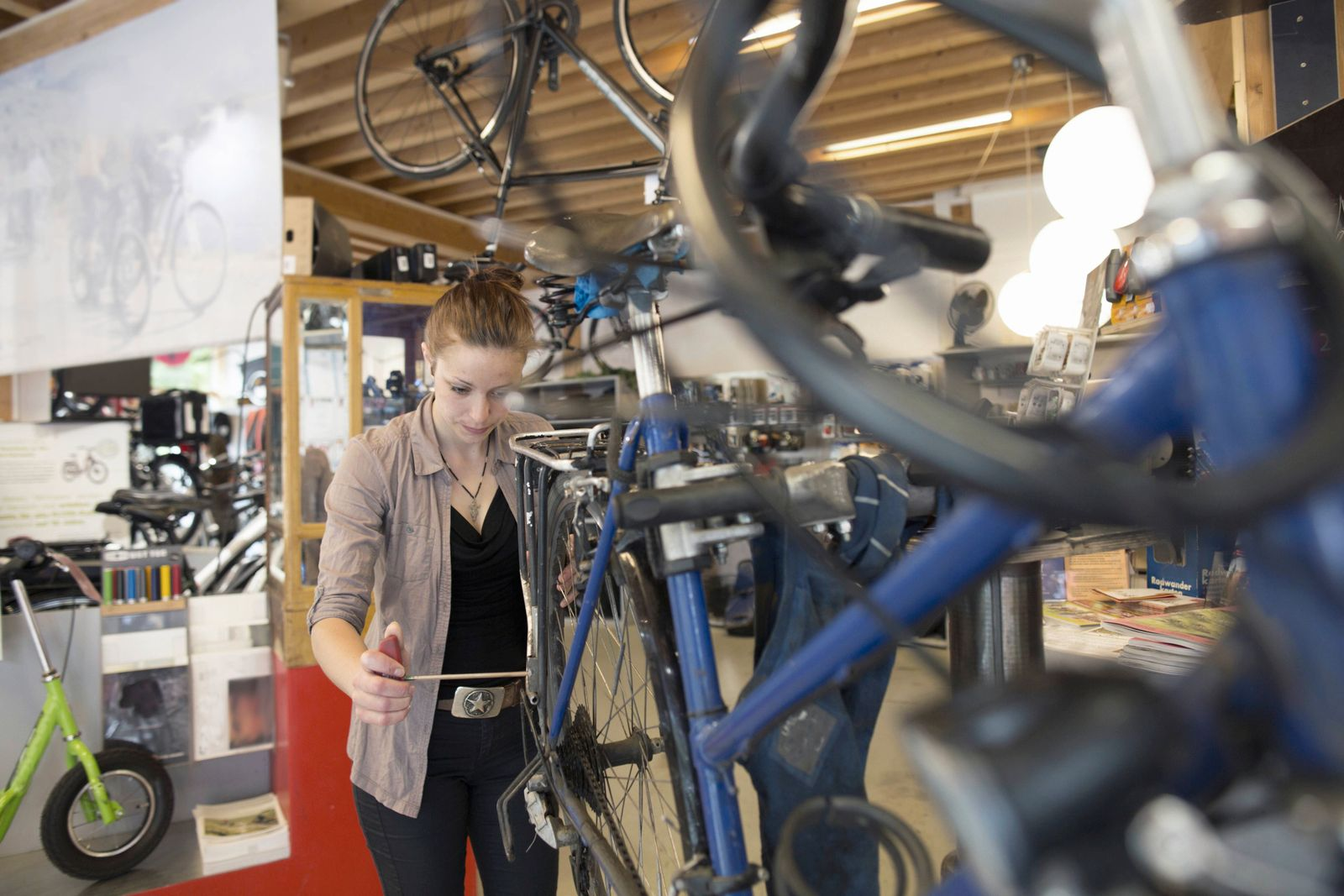 Young woman working in a bicycle repair shop model released Symbolfoto property released PUBLICATION