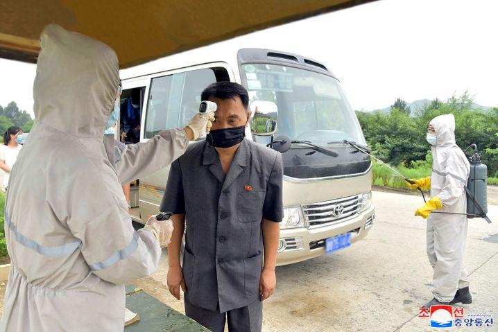 Erhöhte Temperatur? Medizinisches Personal testet einen Mann auf Symptome des Coronavirus