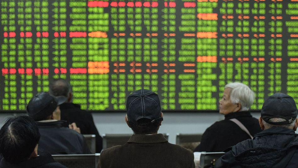 Investoren verfolgen im chinesischen Hangzhou die Börsenentwicklung