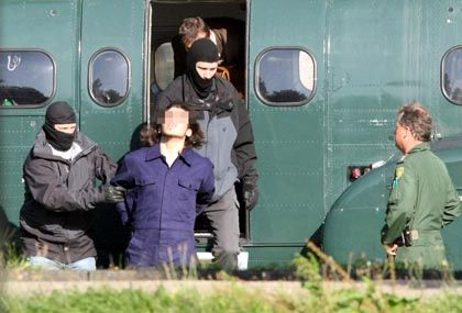 One of the suspects is taken from a helicopter outside the court in Karlsruhe Wednesday.