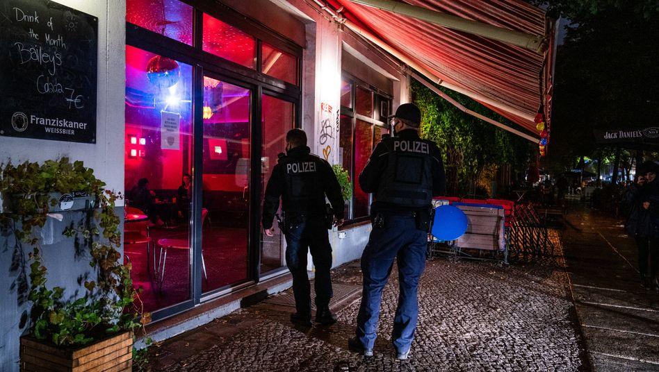 Zwei Polizisten kontrollieren im Stadtteil Friedrichshain die Einhaltung der Sperrstunde