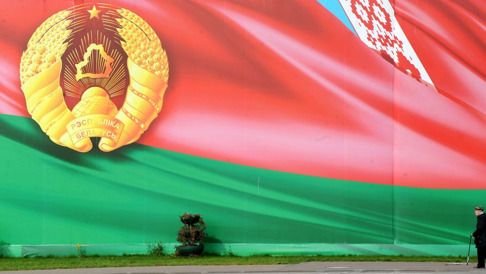 A man walks past a huge image of the Belarus flag and state emblem in Minsk on Monday.