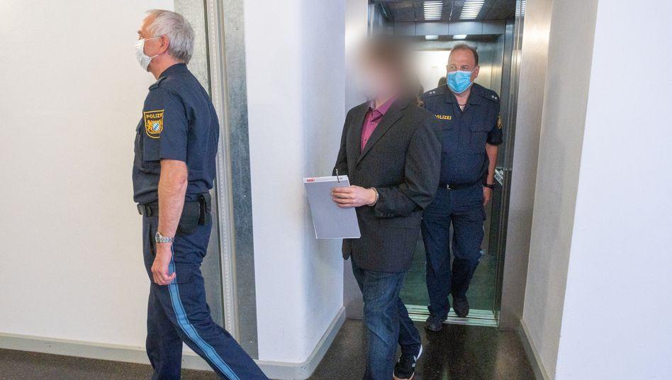 Der Angeklagte (Mitte) wird am 1. Juli von Polizisten in den Gerichtssaal begleitet