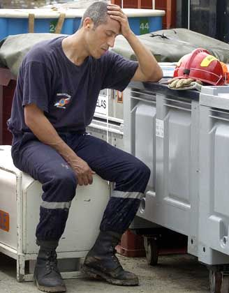A French firefighter takes a rest from unloading heavy equipment to be used in helping in the Aceh relief effort. Red tape could hinder his work in the future.