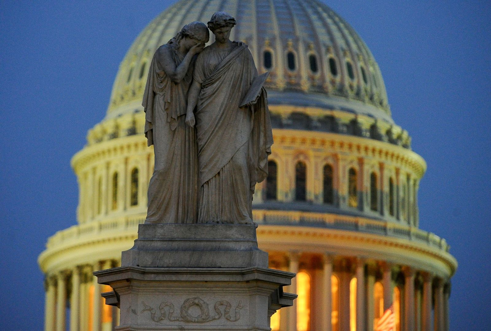 """A statue representing """"Grief"""" lays her covered face on the shoulder of the statue representing """"History"""" on the Peace Monument near the U.S. Capitol where the Senate impeachment trial of President Donald Trump is going on in Washington"""