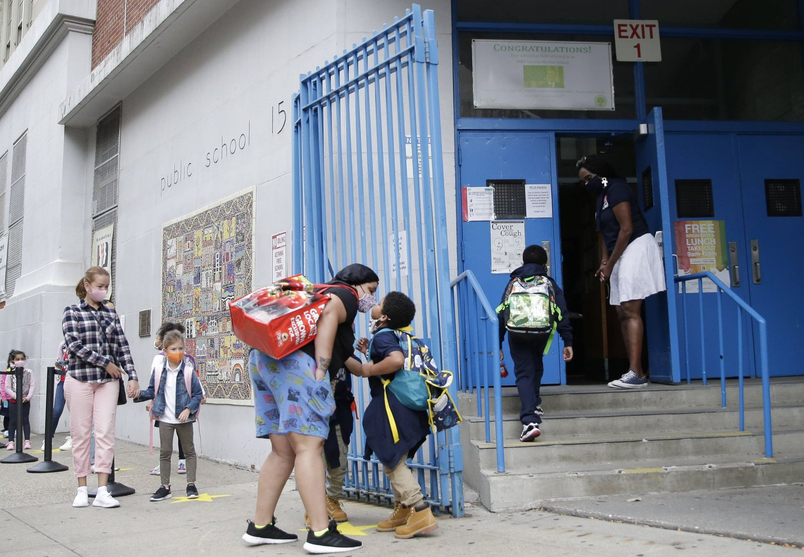 A woman kisses a child before the child enters Public School 15 in New York City on Tuesday, September 29, 2020. Due to