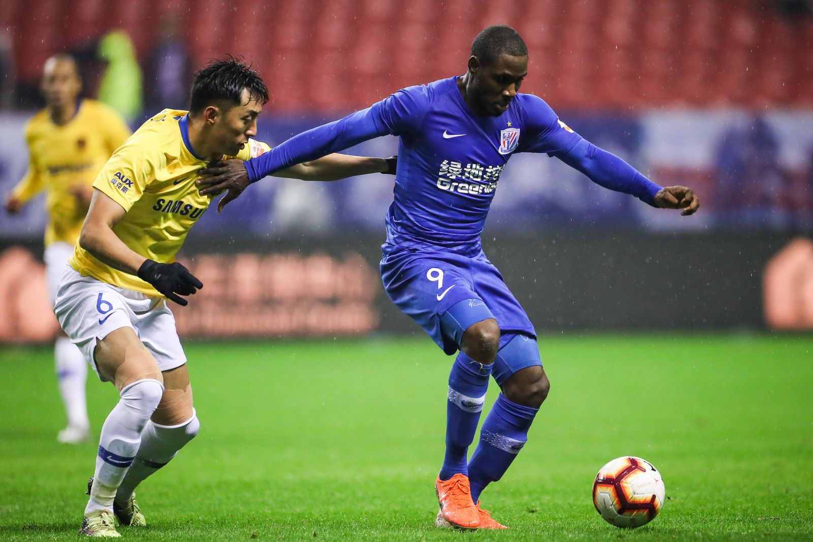 Nigerian football player Odion Ighalo of Shanghai Greenland Shenhua F.C., right, protects the ball during the 29th round