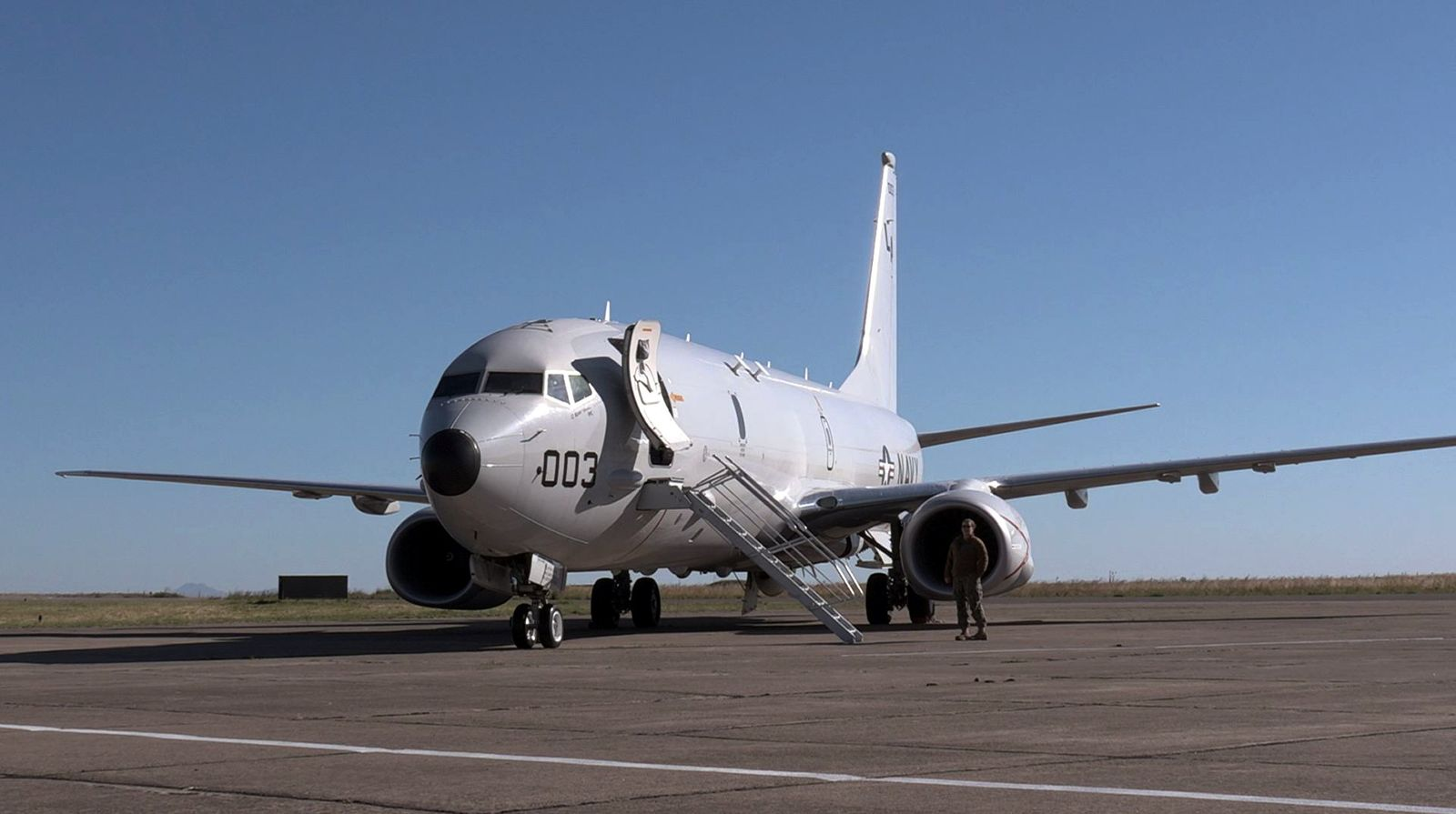 A member of the U.S. Navy stands next to the Boeing P-8A Poseidon plane before its departure to take part in the search for the ARA San Juan submarine missing at sea, at a military air base in Bahia Blanca