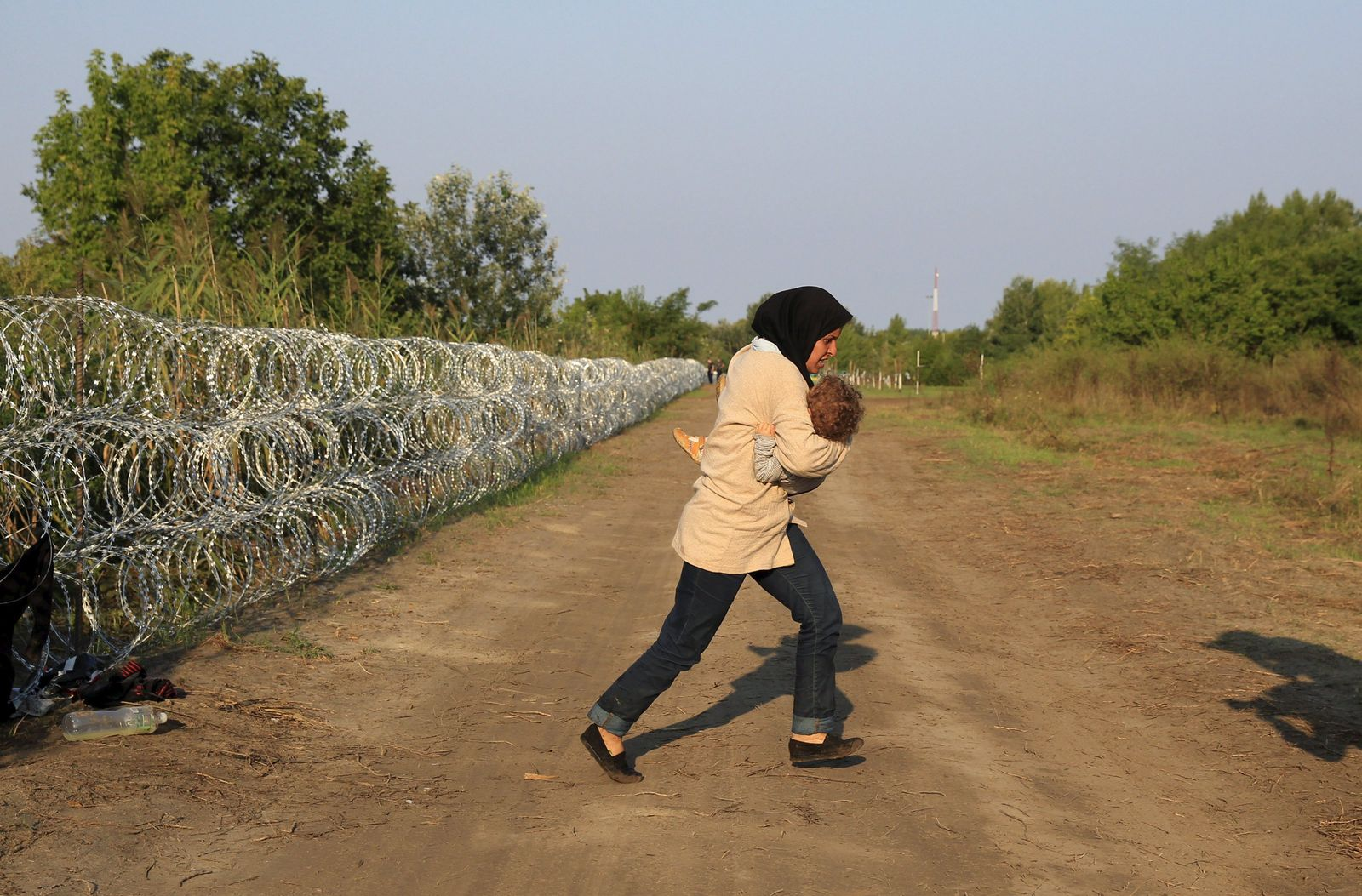 A Syrian migrant runs after crossing under a fence as she enters Hungary, at the border with Serbia, near Roszke
