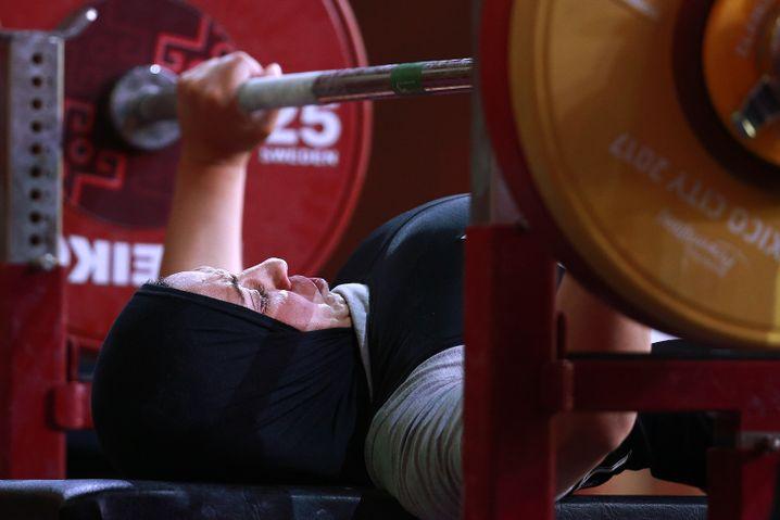 Paralympische Gewichtheberin Rehad Ahmed aus Iran, sie sitzt im Rollstuhl und tritt deswegen im Liegen an