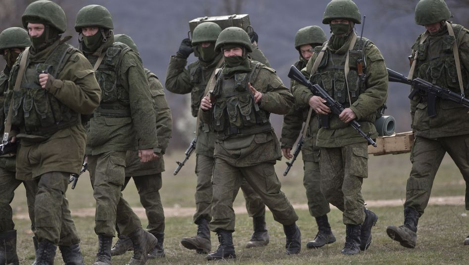 """""""Little green men"""": Pro-Russian soldiers are seen marching near a Ukrainian army base in Perevalne, Crimea, on March 19."""