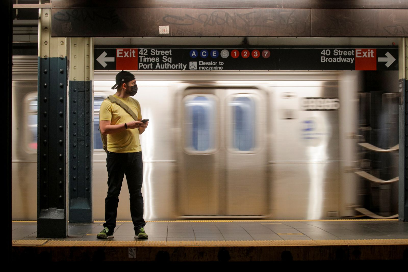 A passenger waits on the platform to ride aboard the MTA's New York City Transit subway, in New York
