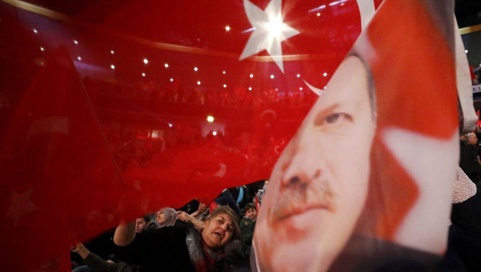 People waving flags depicting the face of President Recep Tayyip Erdogan in Oberhausen, Germany, in February.