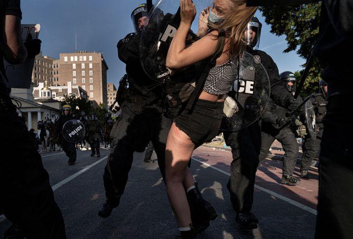 Ein Polizist schubst eine Demonstrantin, während Sicherheitskräfte die Gegend in der Nähes des Weißen Hauses räumten