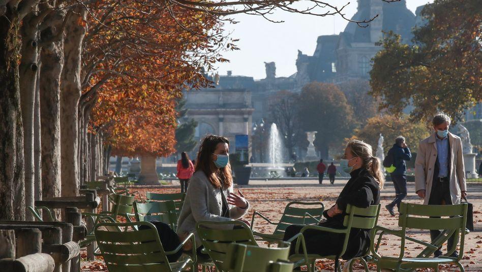 Menschen mit Mundschutz während der Corona-Pandemie vor dem Louvre in Paris