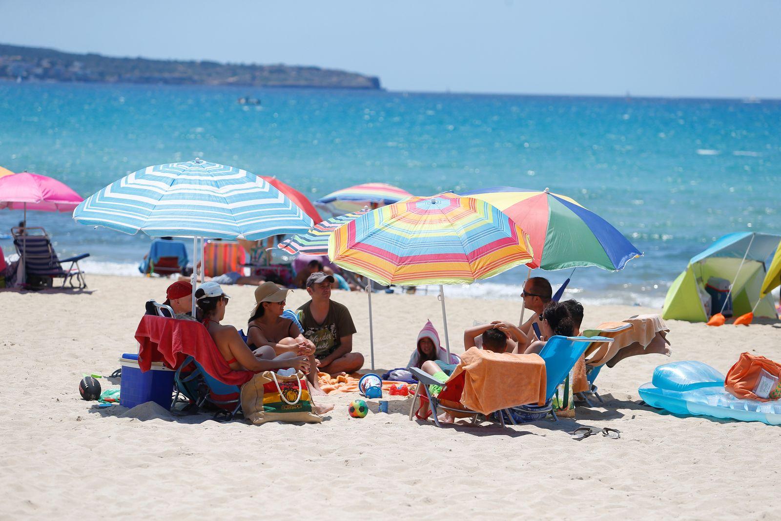 People sunbathe in Playa de Palma beach in Mallorca