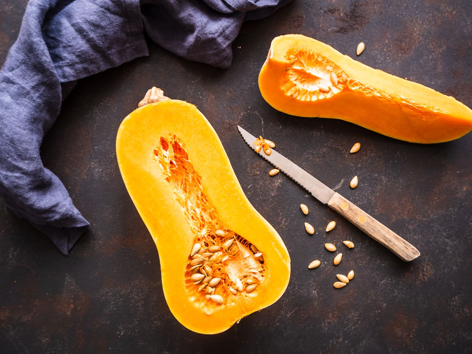 Half a butternut squash on a rustic table with a cloth napkin, top view