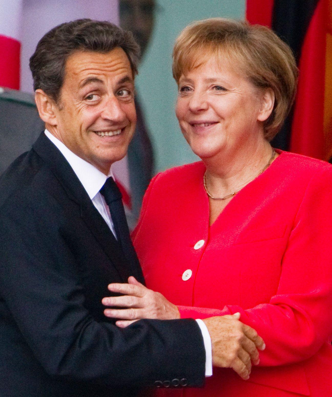 Merkel und Sarkozy lächeln